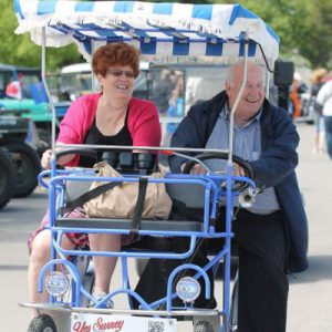 Senior couple laughing riding in blue surrey